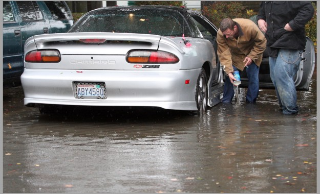 Bill Christman bails out the floor of his car with a drink cup while parked in Poulsbo's Anderson Parkway on Saturday, October 10, 2015. Christman was on break from work when he parked in the lot to take a nap, when he awoke and opened the door water rushed in from the flooded lot. (MEEGAN M. REID / KITSAP SUN)