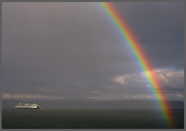 A rainbow streaks across the sky as the Washington State Ferry M/V Spokane heads to Seattle from Bremerton on a stormy Saturday, March 12, 2016. (MEEGAN M. REID / KITSAP SUN)