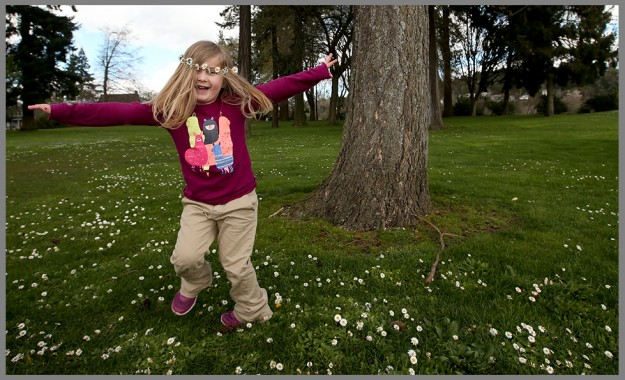 With a chain of daisies on her head, Catalina Gracier, 4, spins around while enjoying a nice day at Evergreen Rotary Park in Bremerton on Tuesday, March 22, 2016. The daisy chain was made by Juliana Guyt, 19, who was approached by the curious youngster as she sat among the flowers linking them together. (MEEGAN M. REID / KITSAP SUN)