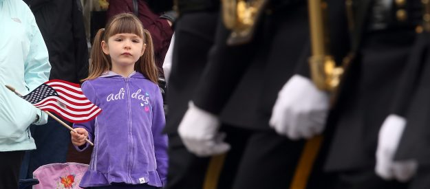 Camryn Baldwin, 5, waves a small flag as the color guard marches past to kick off the start of the Armed Forces Day Parade on 4th. Street in downtown Bremerton, Wash. on Saturday, May 16, 2015. (MEEGAN M. REID / KITSAP SUN)