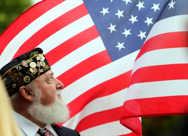 Dave Riley, of American Legion Post 149, glances up as the wind catches the American flag next to him during the Memorial Day ceremony at Ivy Green Cemetery in Bremerton, Wash. on Monday, May 25, 2015. (MEEGAN M. REID / KITSAP SUN)