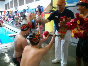 Retiring Nick Giovanni receives flowers from swimmers during the OAC Summer Splash meet in Bremerton on Saturday. (Courtesy photo)