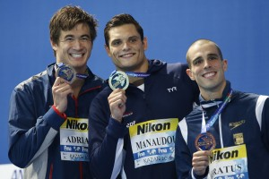 France's gold medal winner Florent Manaudou is flanked by Bremerton's silver medal-winner Nathan Adrian, left, and Brazil's bronze medal winner Bruno Fratus during the ceremony for the 50m freestyle final at the World Swimming Championships in Kazan, Russia, Saturday. (AP Photo/Sergei Grits)