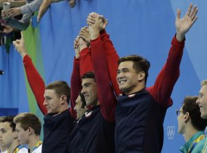 From left to right, United States' Ryan Murphy, Cody Miller, Michael Phelps and Nathan Adrian celebrate winning gold during the medal ceremony for the men's 4 x 100-meter medley relay final during the swimming competitions at the 2016 Summer Olympics, Sunday, Aug. 14, 2016, in Rio de Janeiro, Brazil. (AP Photo/Dmitri Lovetsky)