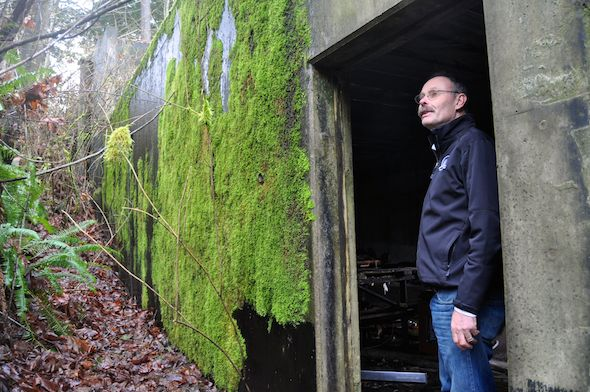 Park staff member John DeMeyer stands at the storage building's mossy entrance.
