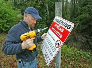 Shawn Ultican of the Kitsap County Health District takes down a warning sign posted on Enetai Creek. Kitsap Sun photo by Carolyn J. Yaschur