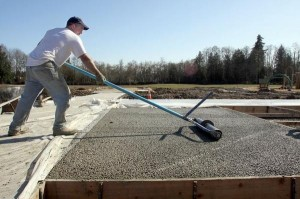 <em>Mike Kithcart rolls a slab of pervious concrete at Bremerton's Blueberry Park.</em> <small>Kitsap Sun photo</small>
