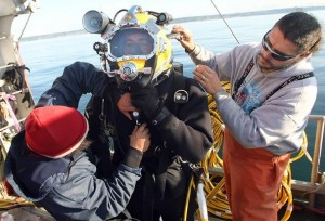 <em>Twila Dawn Captain Steve Sigo (right) and First Mate Aaron Leschi (left) help diver Jake Johnston suit up for his dive at Apple Tree Cove near Kingston on Thursday, when the crew brought up an abandoned fishing net. </em><br><small>Kitsap Sun photo by Meegan M. Reid</small>