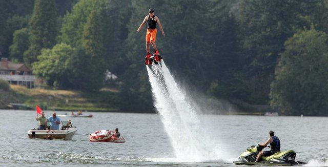 Jerry Johnson of Silverdale takes to the sky above Kitsap Lake on his Flyboard, as boaters stop to watch. Kitsap Sun photo by Larry Steagall