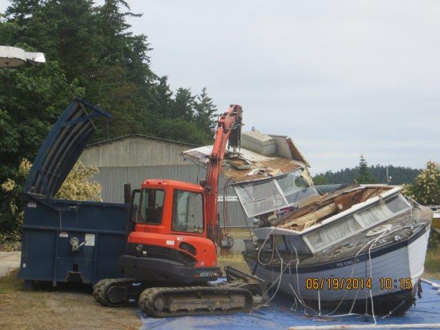 Contractors demolish an old boat turned in as part of a new state program. Photo: Department of Natural Resources