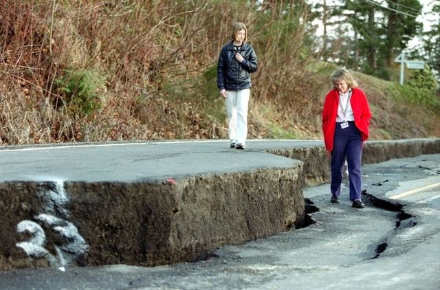 During the 2001 Nisqually earthquake, many roads were damaged. Here, Janine Morris, right, and her daughter, Erin, 12, explore a section of Highway 302 near Victor in Mason County. Kitsap Sun file photo, 2001.