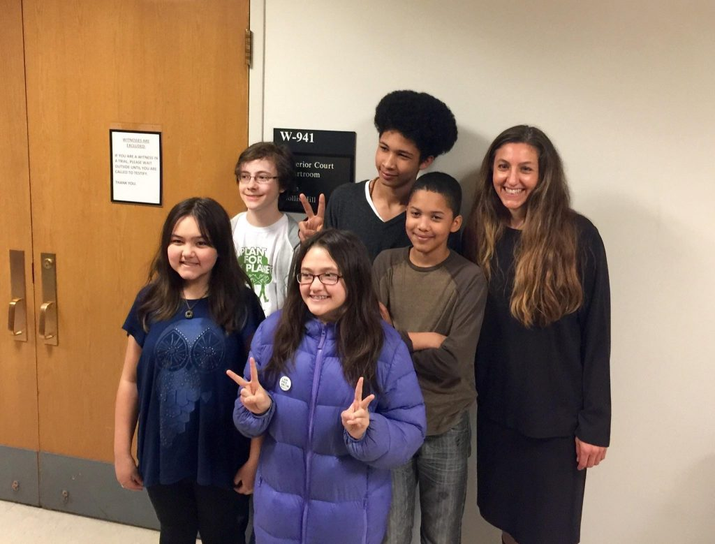 Attorney Andrea Rogers (far right) poses with young plaintiffs outside a King County courtroom. Their legal victory requires state government to address climate change by the end of 2016. Photo: Our Children's Trust