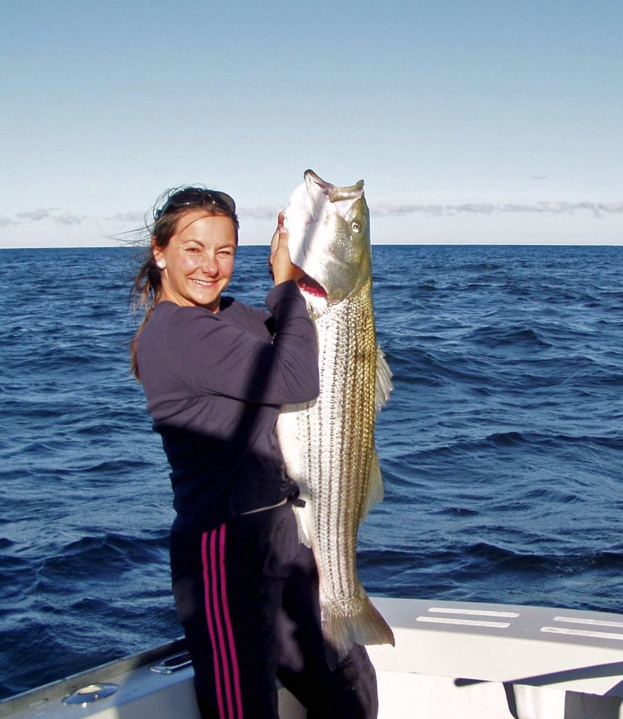 On the East Coast, where they are native, striped bass are one of the most popular sport fish. Here, Angela Anning of Connecticut shows off her impressive striper. On the West Coast, striped bass could be considered an invasive species. Photo: NOAA
